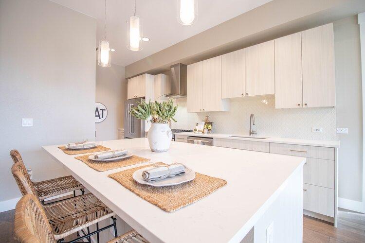 Open concept kitchen with KitchenAid appliances, a gas range, quartz countertops, and a kitchen island.